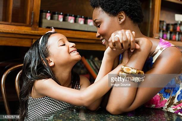 Mutter und Tochter holding Hände im Café