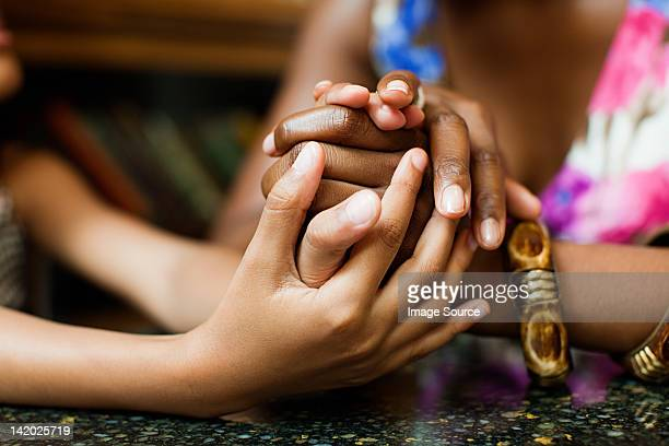 Mother and daughter holding hands in cafe