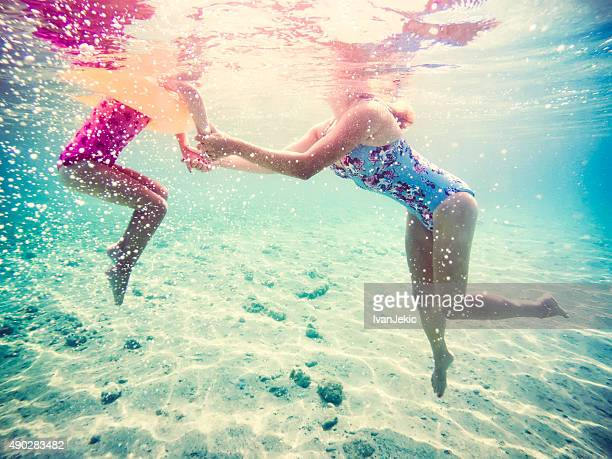 Mother and daughter holding hands in sea together