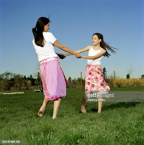 Mother and daughter (9-11) holding hands, spinning in yard