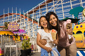 Mother and daughter (8-10)holding ice cream cones at amusement park
