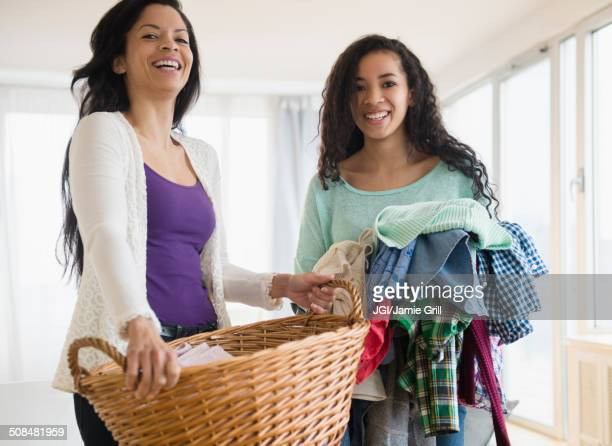 Mother and daughter holding laundry