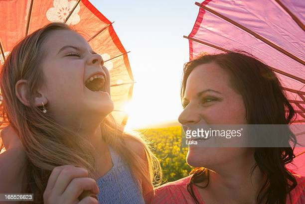 Mother and daughter holding parasols