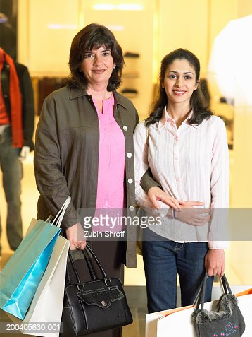 Mother and daughter holding shopping bags in mall, smiling, portrait : Stock Photo