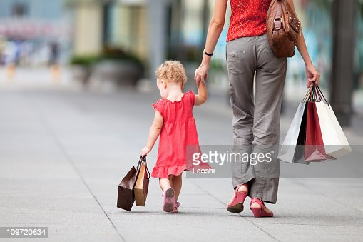 Mother and daughter holding shopping bags : Stock Photo