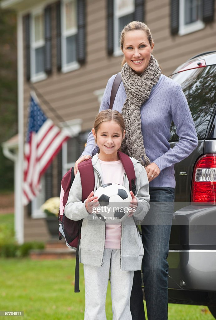 Mother and daughter holding soccer ball