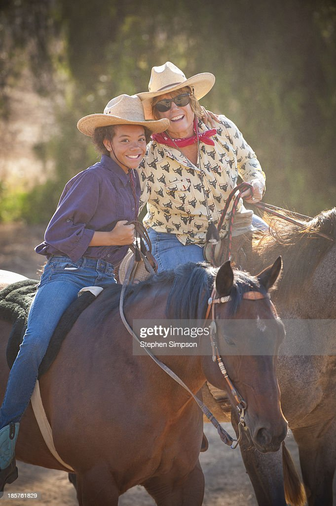mother and daughter horseback-riding : Stock Photo