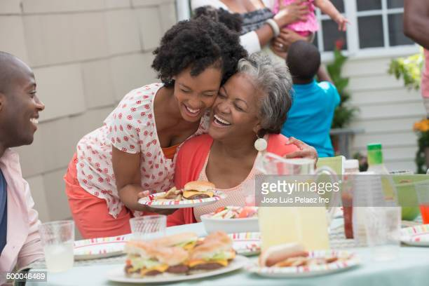 Mother and daughter hugging at barbecue