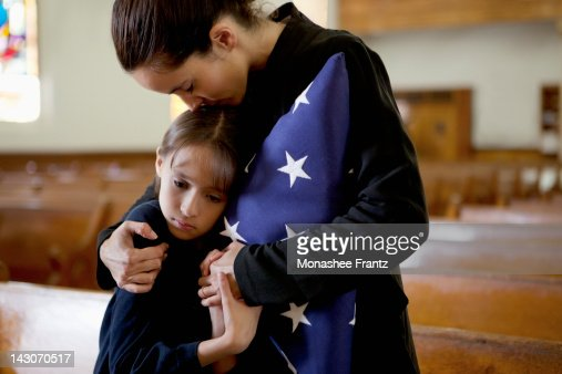 Mother and daughter hugging at military funeral