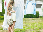 Mother and daughter (4-5) hugging by laundry line