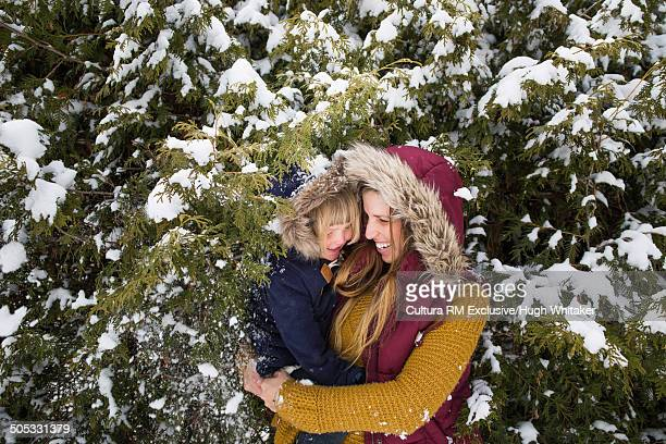 Mother and daughter hugging in winter scene