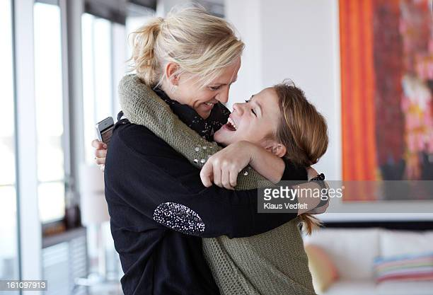 Mother and daughter hugging & laughing together