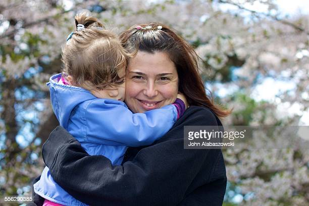 Mother and daughter hugging near cherry blossoms