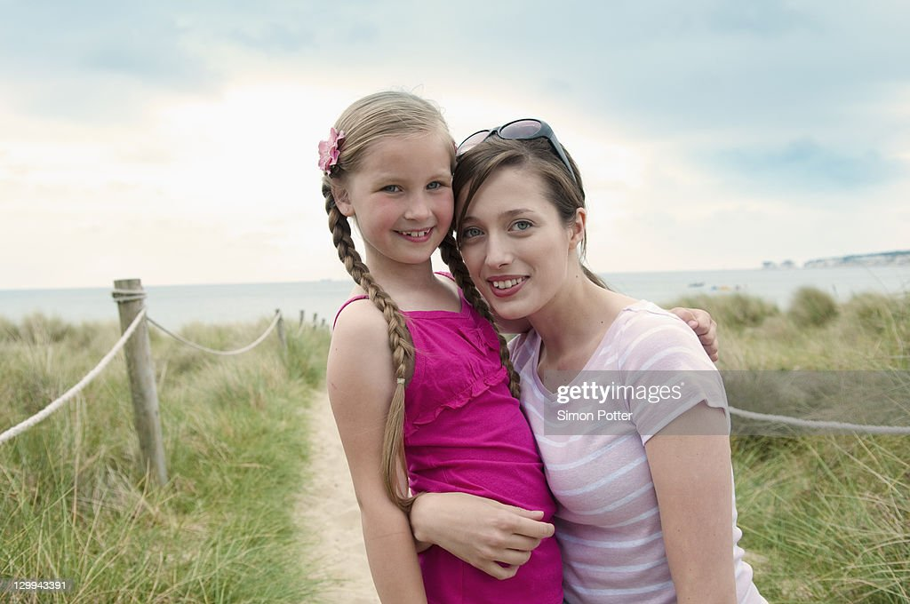 Mother and daughter hugging on beach : Stock Photo