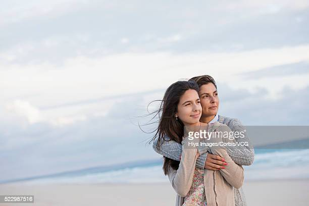 Mother and daughter (13) hugging on beach