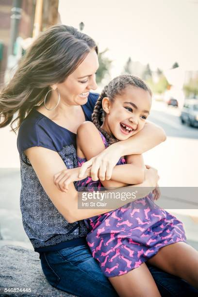 Mother and daughter hugging on sidewalk