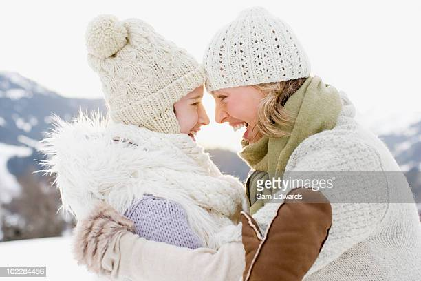 Mother and daughter hugging outdoors in snow