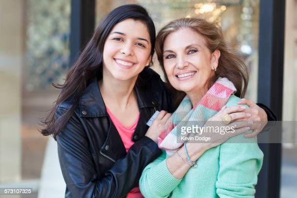 Mother and daughter hugging outside store