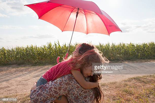 Mother and daughter hugging under red umbrella