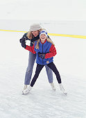 Mother and daughter (13-14) ice skating
