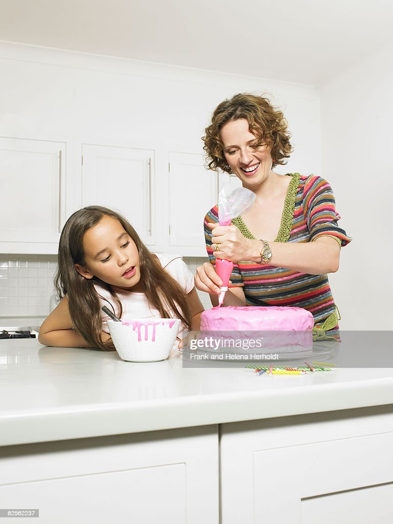 Mother and daughter icing cake