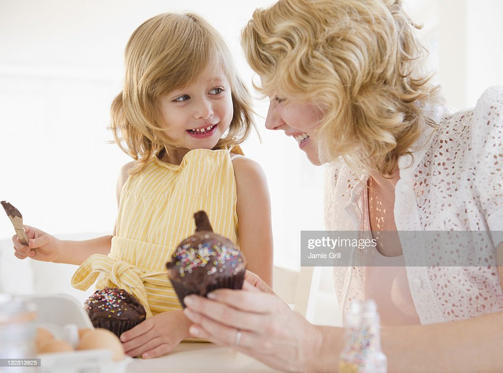 Mother and daughter icing cupcakes together : Stock Photo