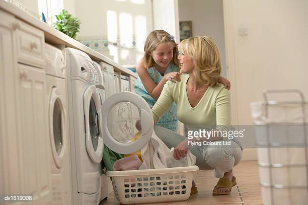 Mother and Daughter in a Utility Room Loading a Washing Machine with Laundry
