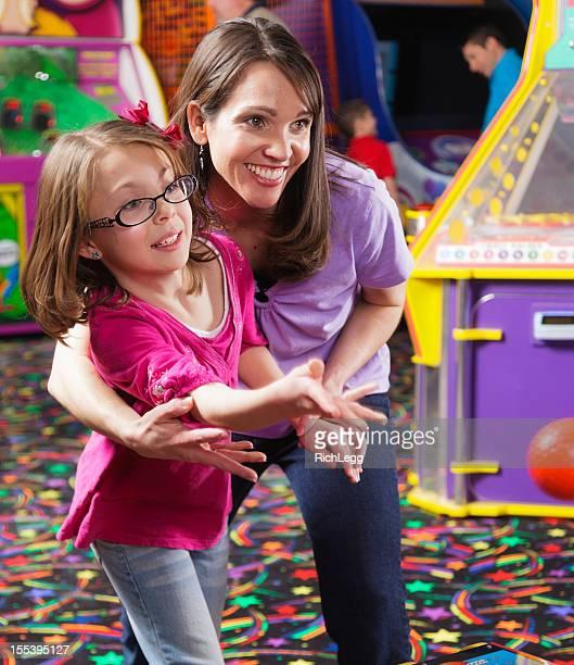 Madre e hija en una sala de máquinas recreativas