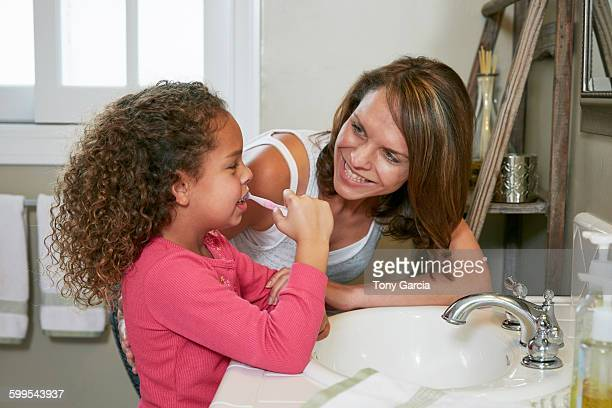 Mother and daughter in bathroom at sink brushing teeth face to face smiling