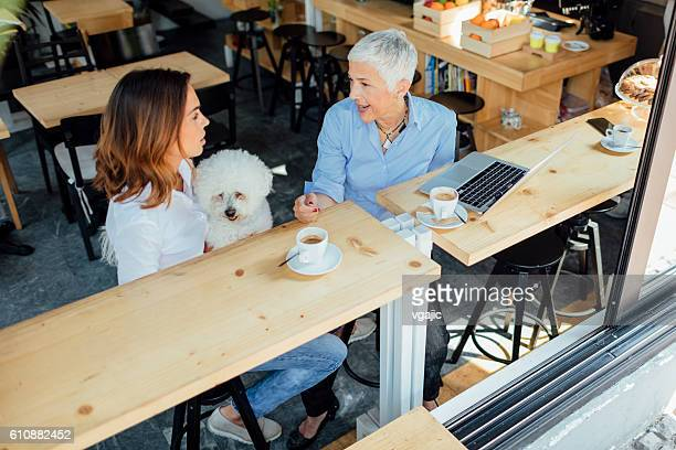 Mother and Daughter In Cafe With Their Dog