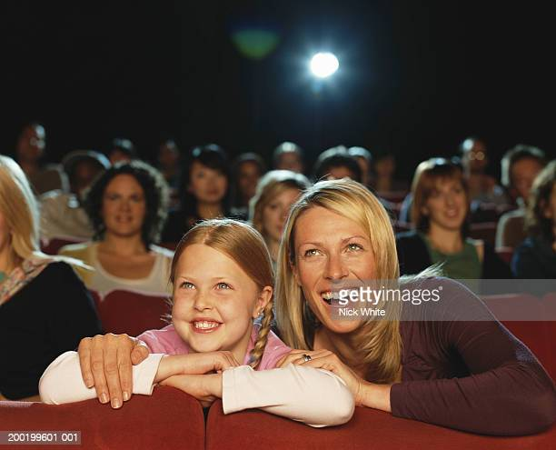 Mother and daughter (7-9) in cinema, laughing, close-up