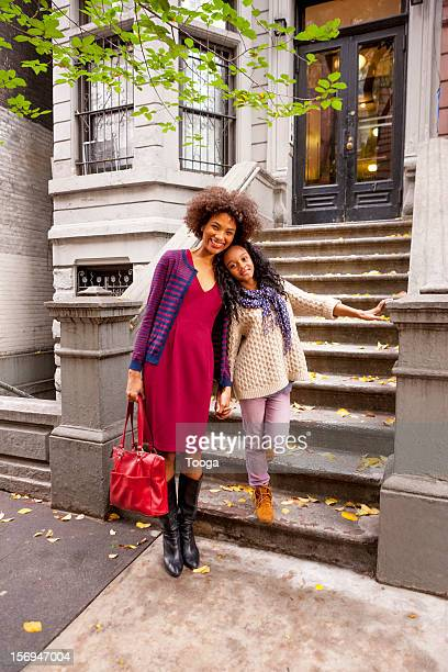 Mother and daughter in front of their home