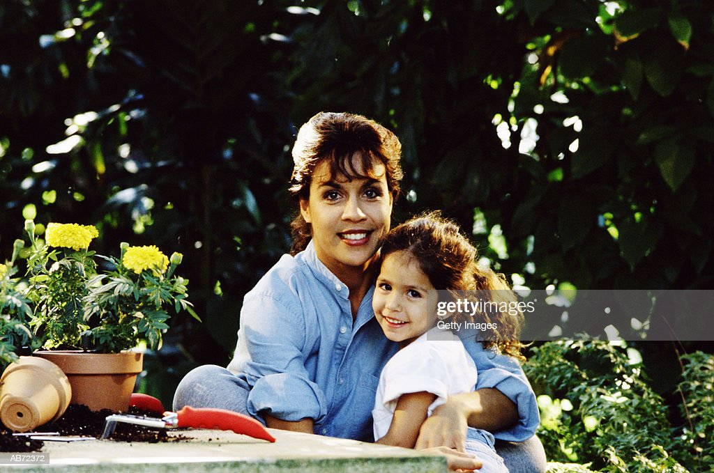 Mother and daughter (4-6) in garden, portrait : Stock Photo