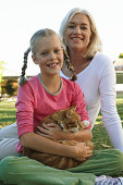 Mother and daughter (10-12) in garden with cat, smiling, portrait