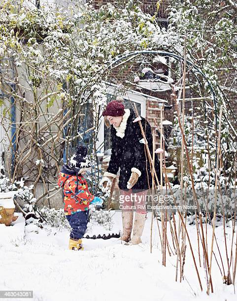 Mother and daughter in garden with snow