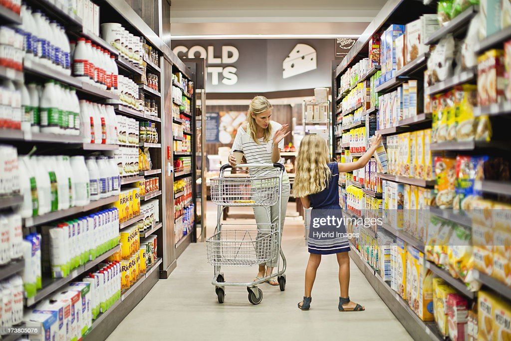 Mother and daughter in grocery store : Stock Photo