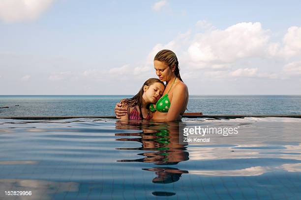 Mother and daughter in infinity pool