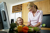 Mother and daughter (5-7) in kitchen by vegetables and laptop