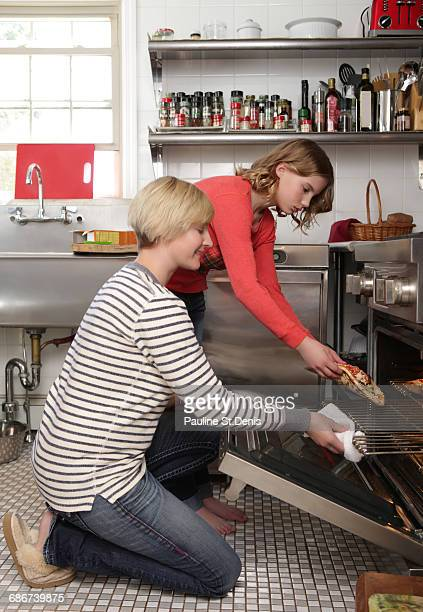 'Mother and daughter in kitchen, placing pizza in oven'