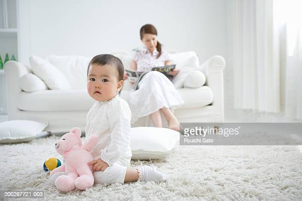 Mother and daughter (6-9 months) in living room (focus on girl kneeling on rug)