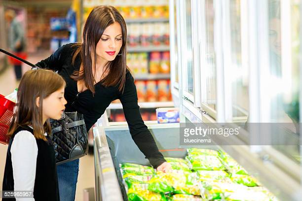 Mother and daughter in supermarket near frozen food