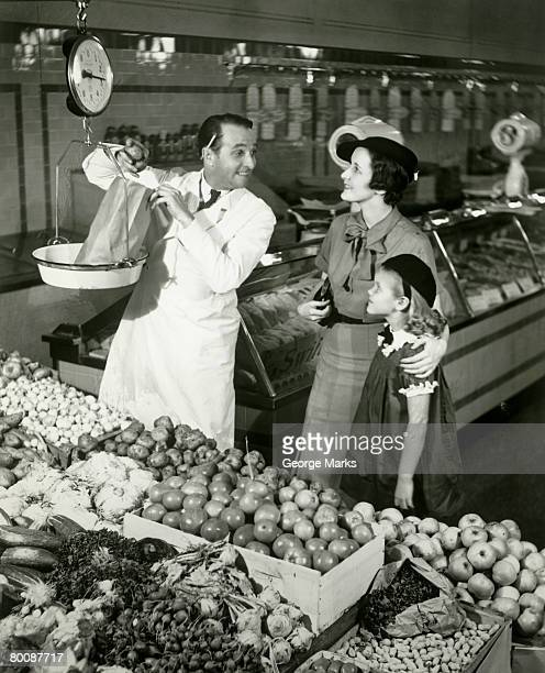 Mother and daughter in supermarket, shop assistant weighing groceries