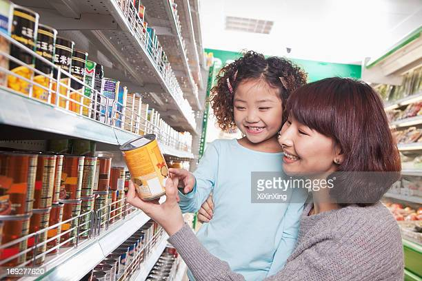 Mother and Daughter in Supermarket Shopping, Looking at a Product