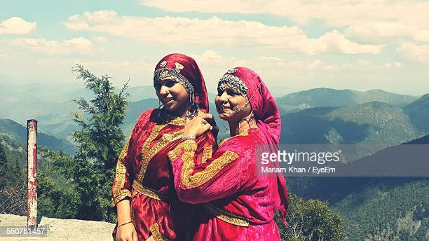 Mother And Daughter In Traditional Clothing Against Mountains