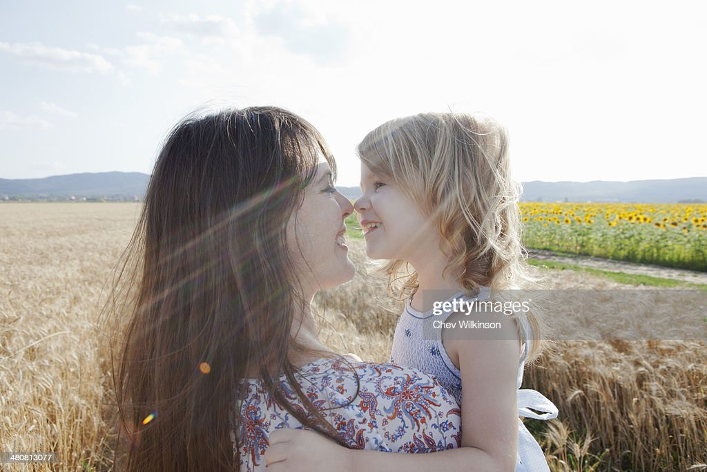 Mother and daughter in wheat field hugging : Stock Photo