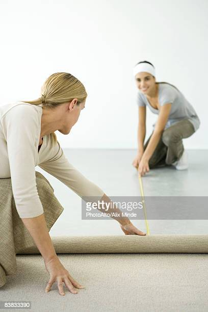 Mother and daughter installing carpet together