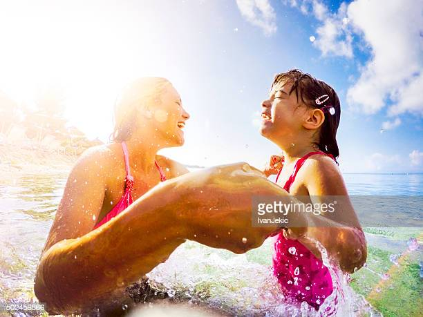 Mother and daughter jumping in sea together and holding hands