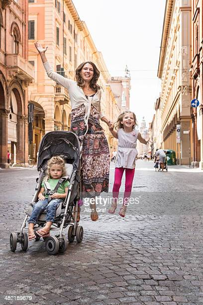 Mother and daughter, jumping in street, Bologna, Italy