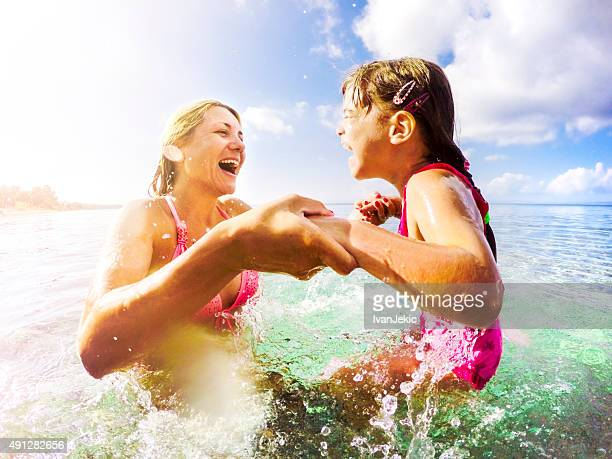 Mother and daughter jumping in the sea together