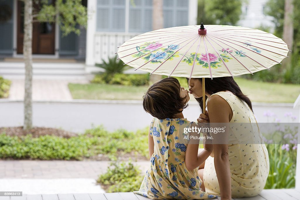 Mother and daughter kiss under umbrella : Stock Photo